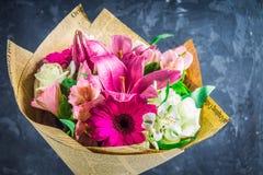 Boeket van bloemen van lelie, gerbera, witte rozen en alstroemeria tegen de achtergrond van een donkere concrete muur Een vakanti Stock Afbeeldingen