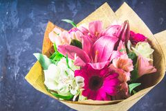 Boeket van bloemen van lelie, gerbera, witte rozen en alstroemeria tegen de achtergrond van een donkere concrete muur Een vakanti Stock Foto's