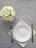 Boeket van bloemen, mes, vork, witte plaat, servet op grijze stoffenachtergrond royalty-vrije stock foto's