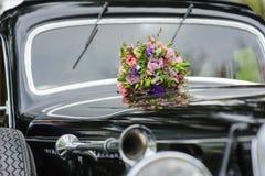 Boeket van bloemen op auto van het kap retro huwelijk royalty-vrije stock afbeelding