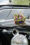 Boeket van bloemen op auto van het kap retro huwelijk royalty-vrije stock fotografie