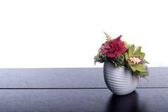 Boeket van bloemen op een bruin bureau met geïsoleerde achtergrond Stock Fotografie