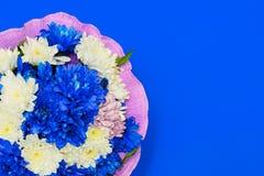 Boeket van chrysanten op een blauwe achtergrond stock fotografie