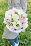Boeket van de close-up het mooie lente in handen gevoelig bloemstuk met roze en groene pastelkleurbloemen Gazon stock afbeeldingen