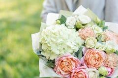 Boeket van de close-up het mooie lente in handen gevoelig bloemstuk met roze en groene pastelkleurbloemen Gazon royalty-vrije stock afbeeldingen