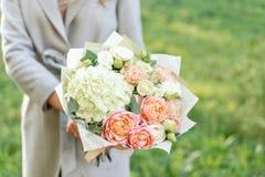 Boeket van de close-up het mooie lente in handen gevoelig bloemstuk met roze en groene pastelkleurbloemen Gazon stock afbeelding