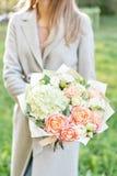Boeket van de close-up het mooie lente in handen gevoelig bloemstuk met roze en groene pastelkleurbloemen Gazon royalty-vrije stock fotografie