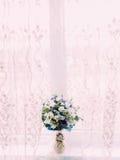 Boeket van de lente violette en witte bloemen in vaas dichtbij het venster royalty-vrije stock foto's