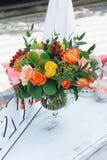 Boeket van Gele en Oranje Bloemen in glasvaas op witte Decoratieve Lijst bij de achtergrond van de Verjaardagspartij royalty-vrije stock foto