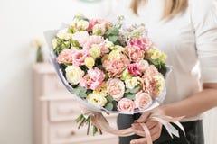 Boeket van gevoelige pastelkleur mooie luxebos van gemengde bloemen in de hand van de vrouw het werk van de bloemist bij a stock afbeelding