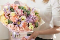 Boeket van gevoelige pastelkleur mooie luxebos van gemengde bloemen in de hand van de vrouw het werk van de bloemist bij a Stock Fotografie