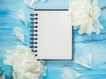 Boeket van het bloeien, witte pioenen en een lege blocnotepagina Stock Afbeeldingen