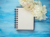 Boeket van het bloeien, witte pioenen en een lege blocnotepagina Royalty-vrije Stock Foto's