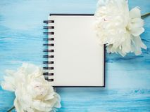 Boeket van het bloeien, witte pioenen en een lege blocnotepagina Royalty-vrije Stock Afbeelding