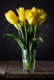 Boeket van mooie verse gele tulpen in dauw op donkere achtergrond stock foto's