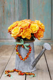 Boeket van oranje rozen in zilveren gieter Stock Afbeeldingen