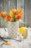 Boeket van oranje tulpen, aangestoken kaars en Paashazen stock afbeelding