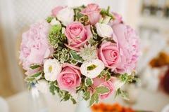 Boeket van pioenen en rozen in een vaas op een gediende lijst stock foto's