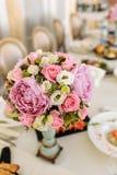Boeket van pioenen en rozen in een vaas op een gediende lijst stock foto