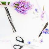 Boeket van purpere bloemen, sjofele banden, klemmen, pen, schaar en notitieboekje op witte achtergrond Vlak leg, hoogste mening stock fotografie
