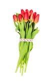 Boeket van rode die tulpen met hartenlint worden verfraaid over wit wordt geïsoleerd Het concept van de Dag van valentijnskaarten Stock Foto's