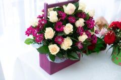 Boeket van rode en witte bloemen in houten vakje op lijst stock foto's