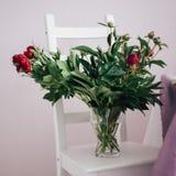 boeket van rode pioenen in een vaas op de witte stoel, huwelijksdecoratie stock fotografie