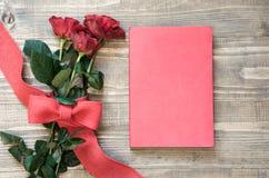 Boeket van rode rozen en rood notitieboekje op houten raad De ruimte van het exemplaar Royalty-vrije Stock Foto