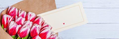 Boeket van rode tulpen voor de dag van de vakantievrouwen en de dag van de valentijnskaart op de achtergrond van houten raad royalty-vrije stock foto