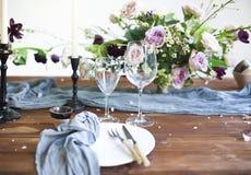 Boeket van roze die bloemen op een lijst voor diner met kaarsen wordt geplaatst Stock Afbeeldingen