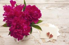 Boeket van roze pioenen in een witte kruik en de witte kaart met de inschrijving en twee decoratieve harten Royalty-vrije Stock Foto's