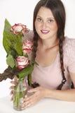 Boeket van roze rozen en donkerbruine jonge vrouw met vlechten Royalty-vrije Stock Afbeelding