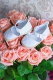 Boeket van rozen en paar schoenen voor een pasgeboren baby royalty-vrije stock fotografie