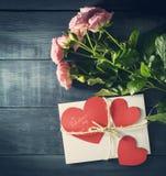 Boeket van rozen met envelop op een blauwe houten achtergrond Stock Afbeeldingen