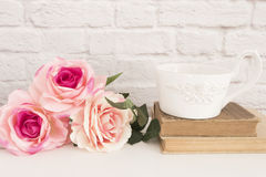 Boeket van rozen op een wit bureau, de grote kop van A van koffie over oude boeken, Romantische bloemenkaderachtergrond, Bloemen  royalty-vrije stock foto