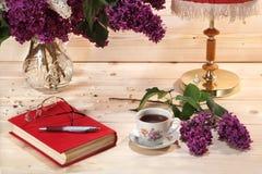 Boeket van seringen, boek, bril, kop thee en schemerlamp stock fotografie