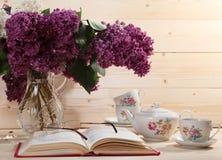 Boeket van seringen, open boek, bril, theepot en kop thee Stock Afbeelding