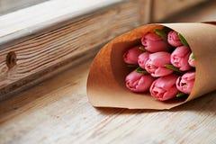 Boeket van tulpen die in document op houten achtergrond worden verpakt Stock Afbeeldingen