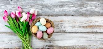 Boeket van tulpen en kleurrijke eieren voor Pasen op wit hout Royalty-vrije Stock Foto's