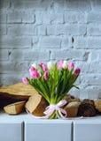 Boeket van tulpen met roze lint op de grijze bakstenen muur backgr stock afbeeldingen