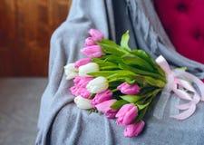 Boeket van tulpen met roze lint op grijze deken Royalty-vrije Stock Foto
