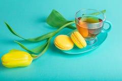 Boeket van tulpen op kleurenachtergrond Thee met gele makarons Stock Afbeelding