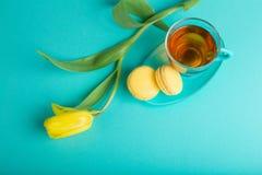 Boeket van tulpen op kleurenachtergrond Thee met gele makarons Stock Foto's