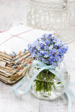 Boeket van vergeet-mij-nietjebloemen in glasvaas, stapel van wijnoogst Stock Afbeelding