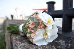 Boeket van verse bloemen dichtbij de meerpaal Huwelijksboeket van rozen en orchideeën Royalty-vrije Stock Foto