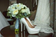Boeket van witte rozen en elegante huwelijksschoenen op houten lijst stock foto's