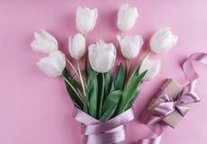 Boeket van witte tulpenbloemen met gift over roze achtergrond Groetkaart of huwelijksuitnodiging stock fotografie