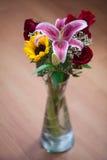 Boeket van zonnebloemen, lelie en rozen in een vaas Stock Fotografie