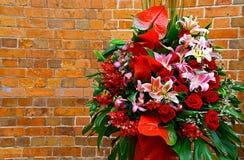 Boeketbloemen tegen curvy bakstenen muur stock foto