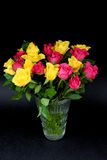 Boeketten van langzaam verdwijnende gele en roze rozen in een glasvaas Royalty-vrije Stock Afbeeldingen